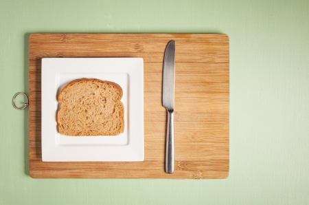 Sliced brown bread on square white plate with  knife on wooden chopping board Stock Photo