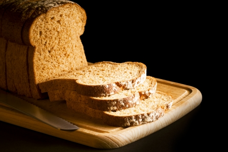Brown wholemeal sliced bread loaf on wooden chopping board with chef s knife