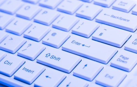 Close up of white keyboard  with blue lighting effect for concepts of digital technology