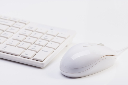 Close up of white wireless keyboard  and wired mouse with shallow depth of field
