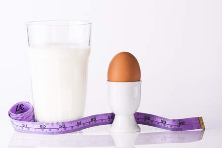 Glass of milk with boiled egg in white egg cup and measuring tape