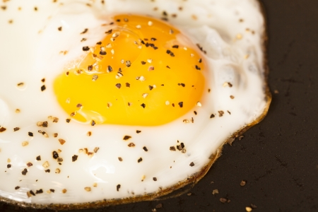 peppered egg frying in pan sunny side up Stock Photo