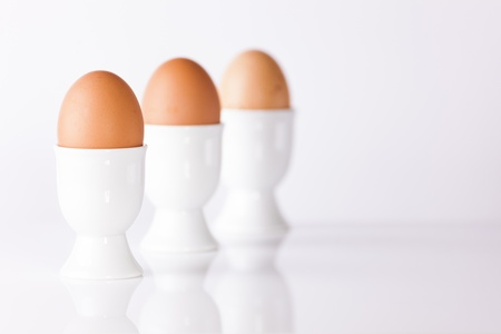 Three boiled eggs in white egg cups on plain white background shallow depth of field Stock Photo