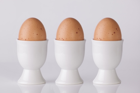 Three boiled eggs in white egg cups on plain white background Stock Photo