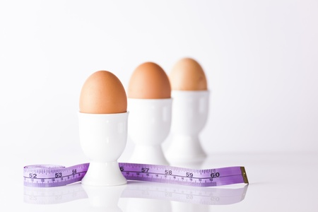 Three boiled eggs in white egg cups with measuring tape signifying weight loss