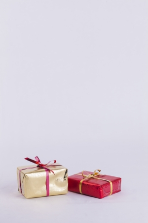 recieving: Wrapped red and gold christmas presents on white background with copy space Stock Photo