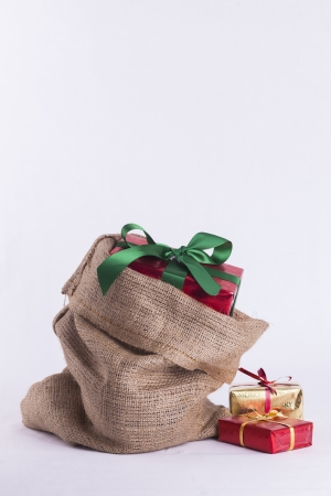 Wrapped Christmas present in Hessian sack with extra gifts on white background Stock Photo - 23989543