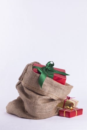 Wrapped Christmas present in Hessian sack with extra gifts on white background Stock Photo - 23989550