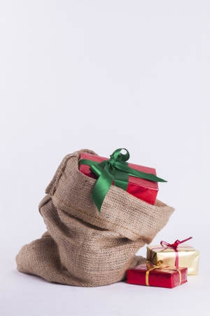 Wrapped Christmas present in Hessian sack with extra gifts on white background Stock Photo - 23989546