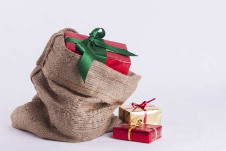 Wrapped Christmas present in Hessian sack with extra gifts on white background Stock Photo - 23989547