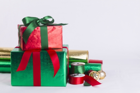 Christmas gifts and wrapping paper with ribbon spools and bells Stock Photo - 23989549