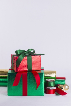 Christmas gifts and wrapping paper with ribbon spools and bells Stock Photo - 23989551
