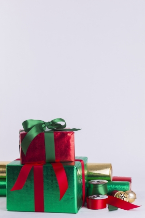 Christmas gifts and wrapping paper with ribbon spools and bells Stock Photo - 23989552