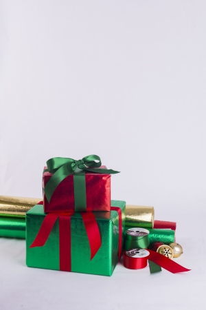 Christmas gifts and wrapping paper with ribbon spools and bells Stock Photo - 23989553