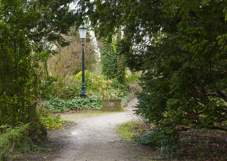 lampost: Entrance to pretty public park in Brugges Belgium with trees and pathway and lampost