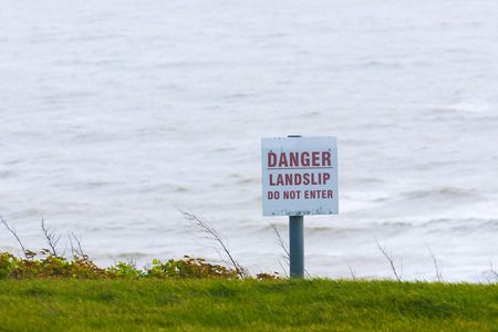 landslip: Danger sign for public information sign next to sea cliff at Folkestone in Kent, England Stock Photo