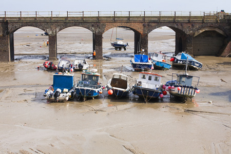Fishing boats at low tide by the old railway viaduct at Folkestone harbour, Kent, UK