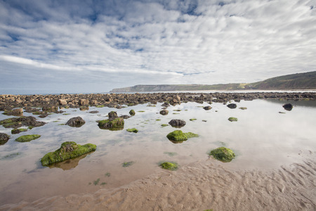 Coastal Beach with rocks and reflections in the sand at Scene Cayton Bay, Scarborough, North Yorkshire, East Coast, UK. landscape Format photo