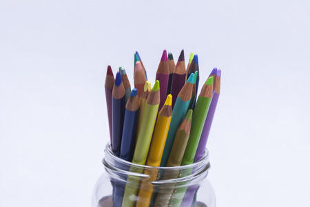 Artists coloured pencils in glass jar on white background for hobbies and leisure time