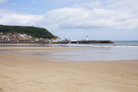 north yorkshire: Beach and lighthouse at Scarborough, North Yorkshire, United Kingdom for family holidays and vacations Stock Photo