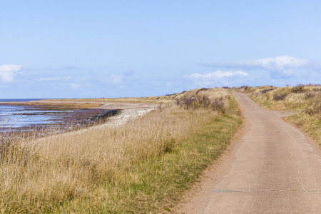spurn: Road over tidal crossing, mud flats and blue sky in spring at Spurn Point nature reserveUK