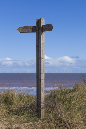 spurn: Wooden sign post at Spurn Point nature reserve with offshore wind farm in background, Yorkshire, Great Britain Stock Photo