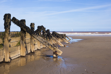 environmental issues: Wooden wave breakers on beach at seaside resort, environmental preservation issues Stock Photo