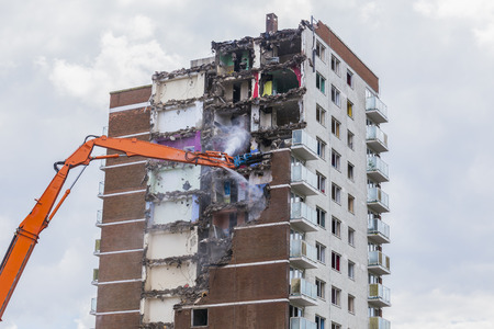 deconstruction: Construction work demolishing high rise flats signifying housing and regeneration