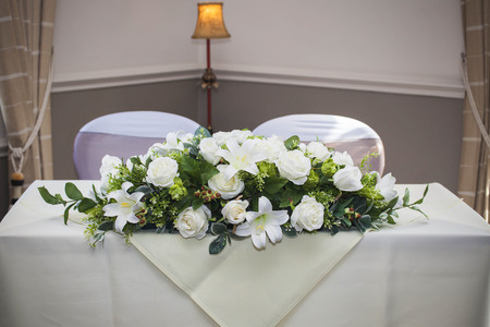 vows: Wedding altar with white roses and lillies in bouquet ready for bride and groom Stock Photo