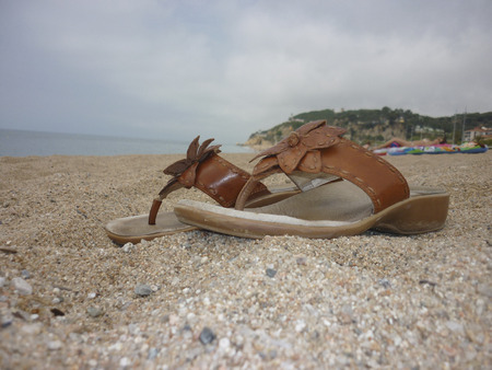 flip flops: Leather flip flops on sandy beach in Calletta, Spain for travel and tourism, holidays and vacations Stock Photo