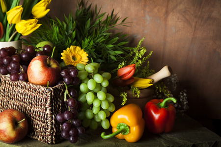 harvest: Traditional basket of harvested fruit and vegetables with flowers and foliage signifying healthy eating Stock Photo
