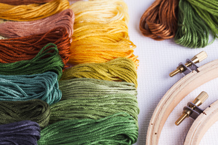 hoops: Embroidery threads with wooden hoops and cross stitch fabric for concepts of leisure time and needlecrafts