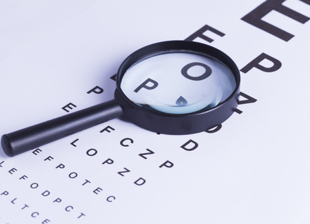 blurred vision: Magnifying glass and eye test for concepts of medicine and health visual aids