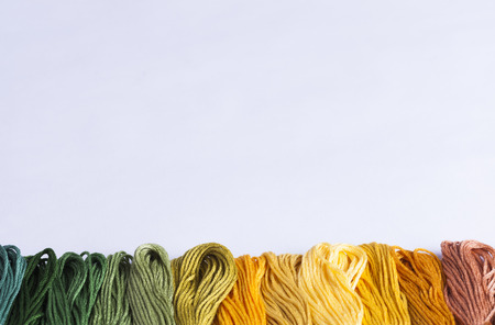 multicolored embroidery threads on white background for concepts of needlecrafts and domestic chores Stock Photo