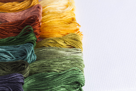 domestic chores: multicolored embroidery threads on white background for concepts of needlecrafts and domestic chores Stock Photo