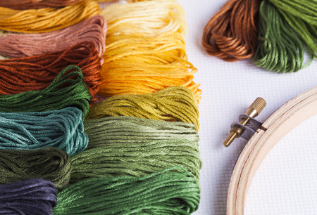 Embroidery threads with wooden hoops and cross stitch fabric for concepts of leisure time and needlecrafts