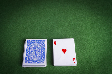 Split pack of playing cards showing Ace of Hearts on green felt card games table Stock Photo