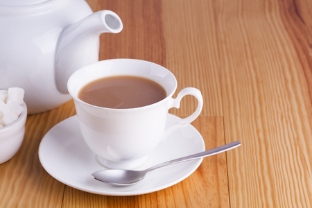 Cup of traditional English Tea with spoon and bowl of sugar cubes
