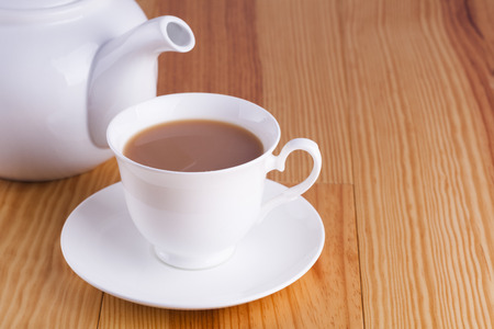 Cup of traditional English Tea with teapot on wooden table background