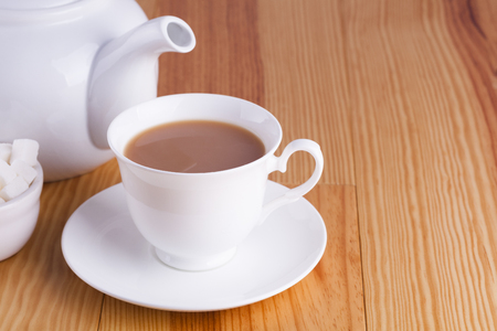 drink me: Cup of traditional English Tea with bowl of sugar cubes and teapot Stock Photo