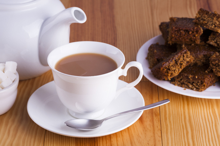drink me: Cup of English Tea with Cake for Tea Break in Afternoon with silver spoon and bowl of sugar cubes Stock Photo