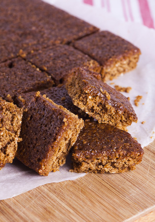 Traditional Yorkshire Parkin for Bonfire Night pm wooden chopping board with red and white striped background signifying home baking and nutrition Stock Photo