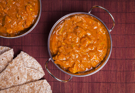 piri: Traditional Chicken Tikka Masala Curry on Rattan Background for asian cooking, takeaways and healthy eating