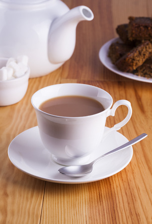 Cup of English Tea with Cake for Tea Break in Afternoon with silver spoon and bowl of sugar cubes Stock Photo