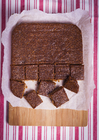 bonfire night: Traditional Yorkshire Parkin for Bonfire Night pm wooden chopping board with red and white striped background signifying home baking and nutrition Stock Photo