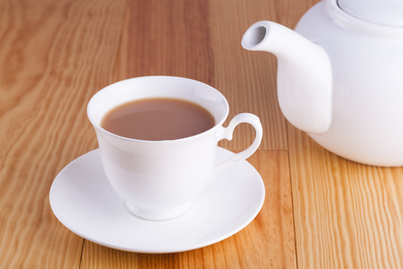 drink me: Cup of traditional English Tea with teapot on wooden table background