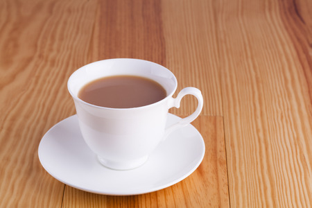 Cup of traditional English Tea in white china cup on wooden table background