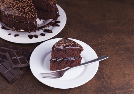 Luxurious Rich Chocolate  Cake on White Plate for concepts of food and indulgence Stock Photo