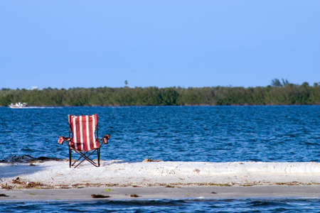 Pool chair abandoned on a deserted sandbar