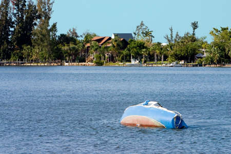 Sunken and abandoned sailboat backdropped with impressive waterfront homes Stock Photo - 390941
